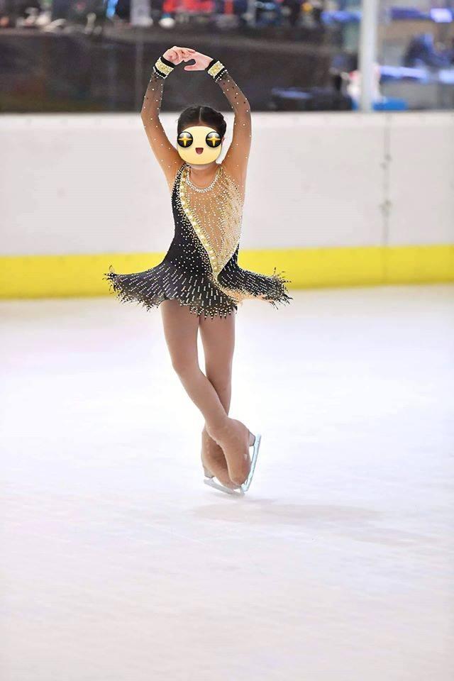Девочка катается на льду в новом платье для фигурного катания