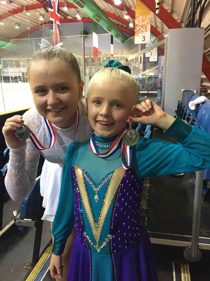 Romy and sister Hallie standing together after winning gold and silver at a figure skating competition