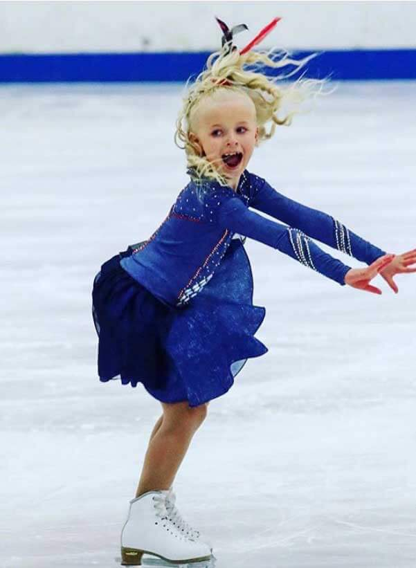 Romy Davies-Jeans in blue figure skaters dress at a national figure skating competition