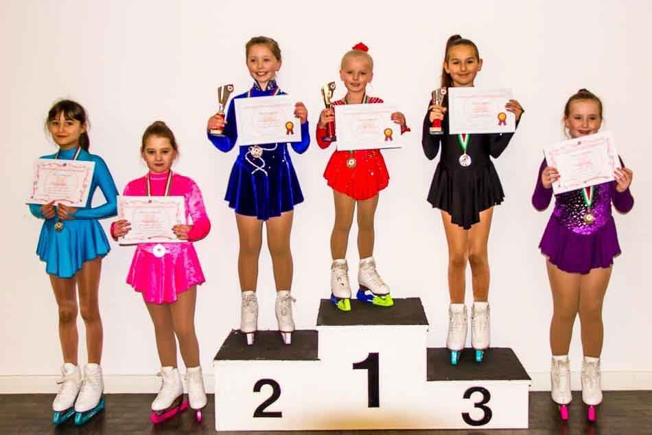 Romy wins her first figure skating club competition and stands for Gold on the podium.