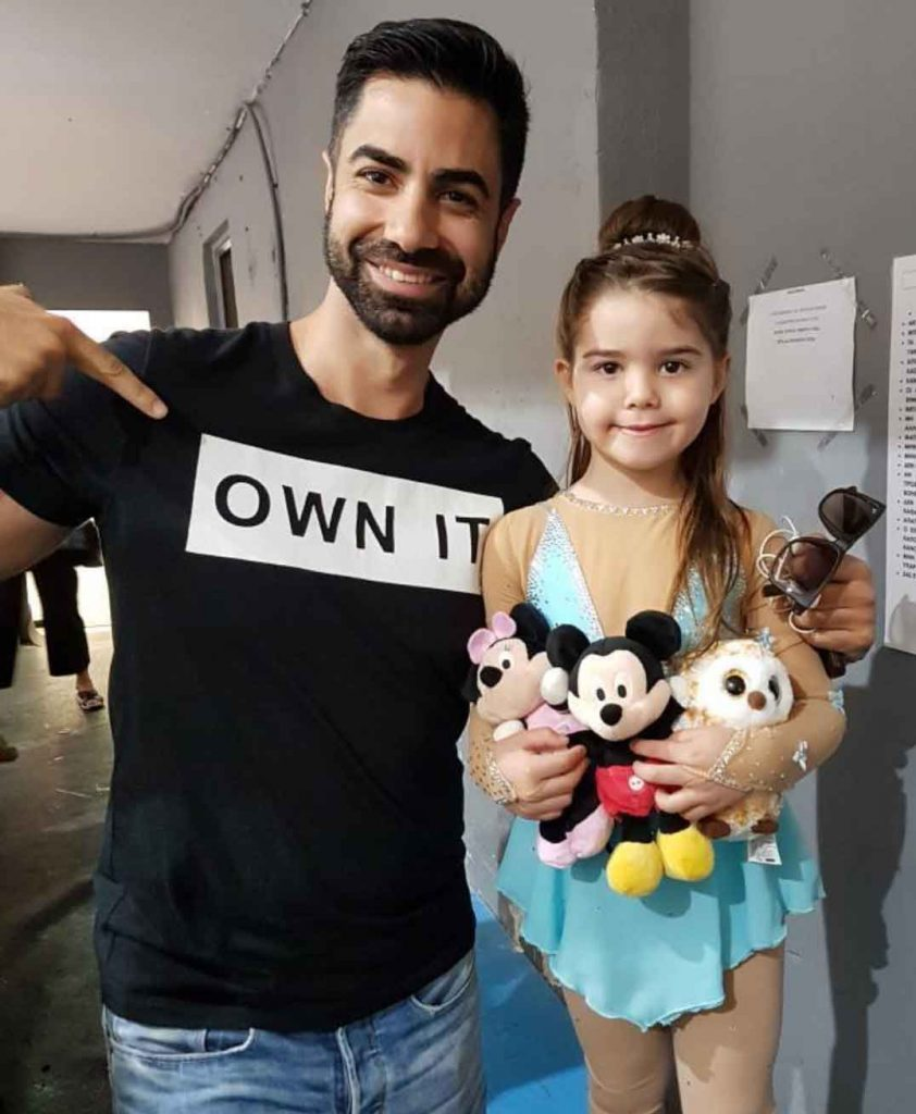 Greek Figure champion with a handful of soft toy animals given by fans