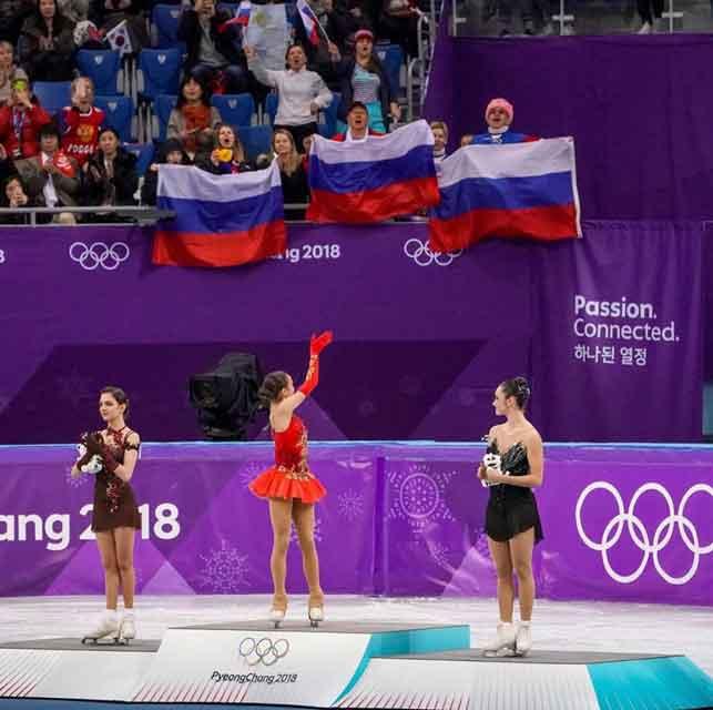 Alina Zagitova on the podium waving to Russian supporters